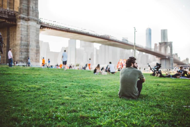 Man sitting on grass near a Brooklyn bridge.