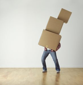 A man struggles with boxes while moving to Brooklyn from Seattle.