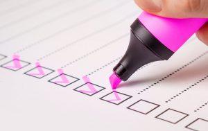 A pink marker making checks on a checklist.