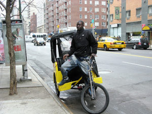 A man standing on a pedicab in NYC