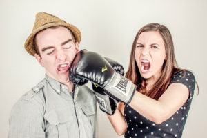 A girl puching a guy with a boxing glove