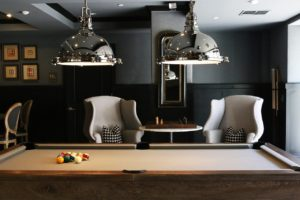A pool table, two chairs and a small table in the background