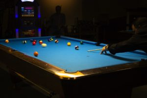 Two people playing pool after helping their friend move a pool table