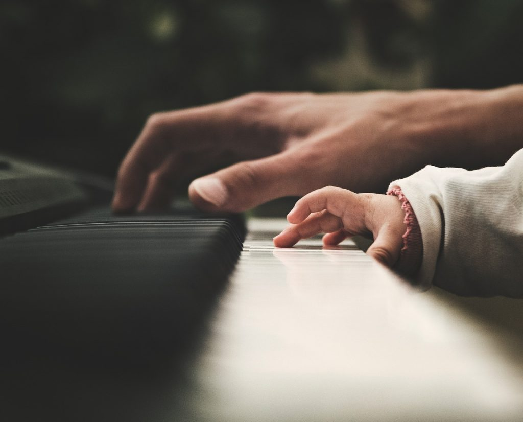 man and a child playing a piano