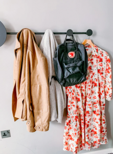 A coat rack with jackets and a bag.