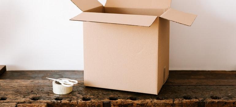 Cardboard box, tape and scissors