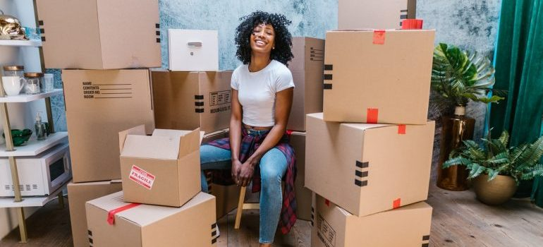 Girl sitting and smiling surrounded by boxes, satisficed that she knew where to find packing supplies in Brooklyn