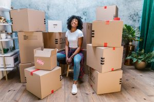 Girl sitting around recycled moving boxes