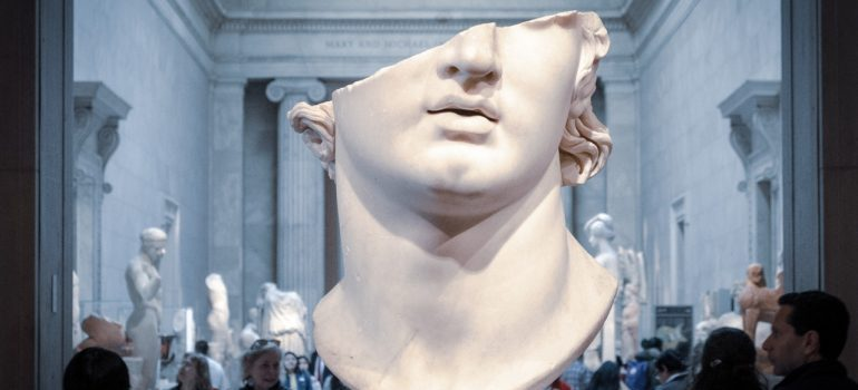 White head bust surrounded by people in a museum