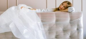 Woman resting her head on a headboard wrapped in bubble wrapa