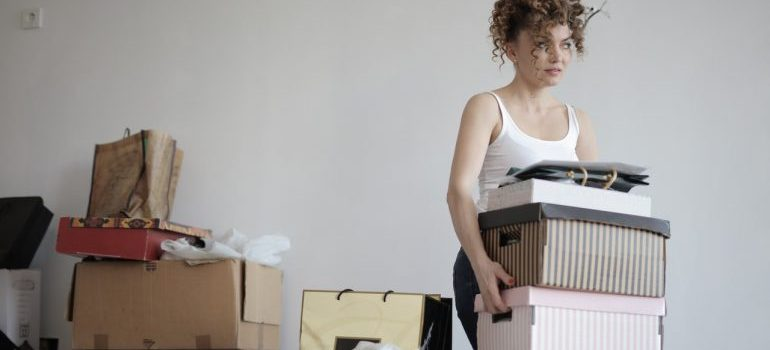 A woman carrying a few boxes stacked on top of one another representing room by room packing