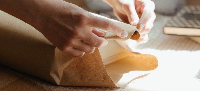 Person wrapping an object in packing paper