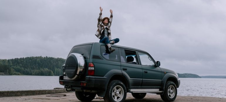 A girl sitting on top of her car near a waterfront