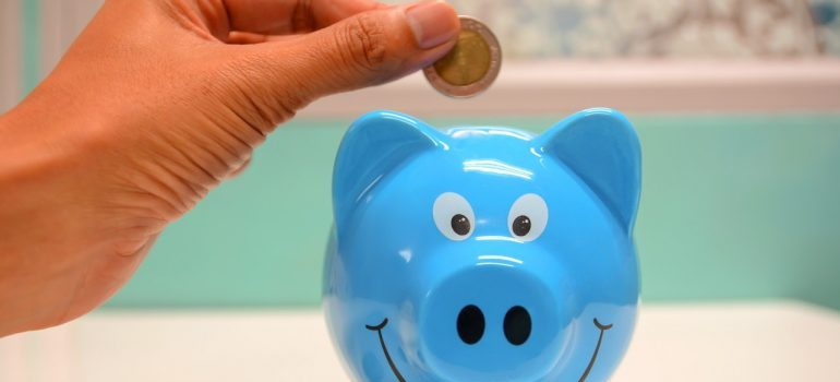 Person putting a coin in a blue piggy bank