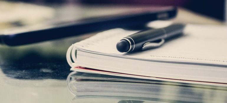 A notebook with a pen laid on it on a glass table