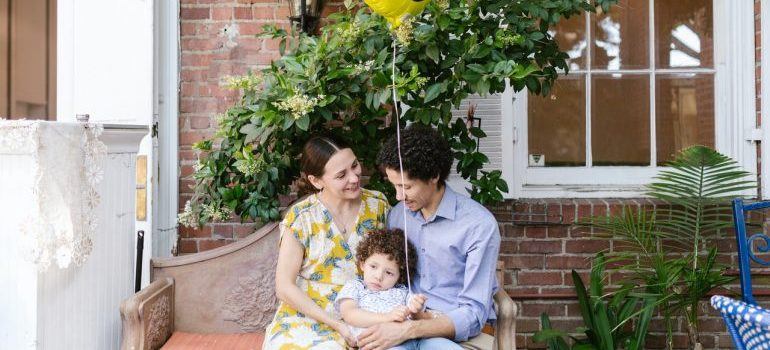 A family of three holding a balloon and sitting in front of their new house representing moving from Brooklyn to NYC suburbs