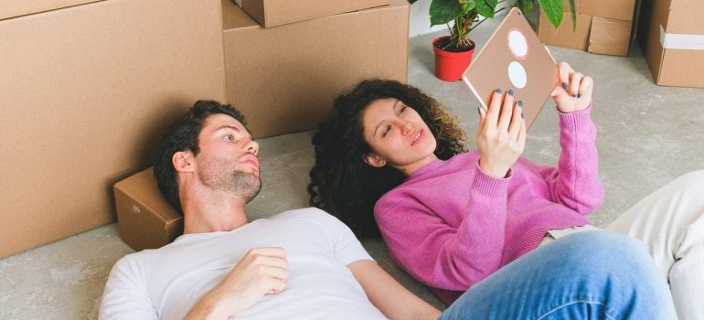 A couple lying on the floor looking at a notebook, with some cardboard boxes behind them