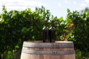 Bottles on a barrel which you will need to pack when moving a wine collection.